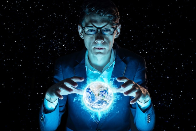 Manngeschäftsmannhändchenhalten überreicht eine blaue glühende kugel in form von planetenerde. elemente von der nasa eingerichtet