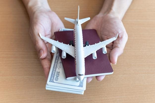 Mannhände, die 100 dollarnoten und flugzeug auf holztisch halten. reisekonzept