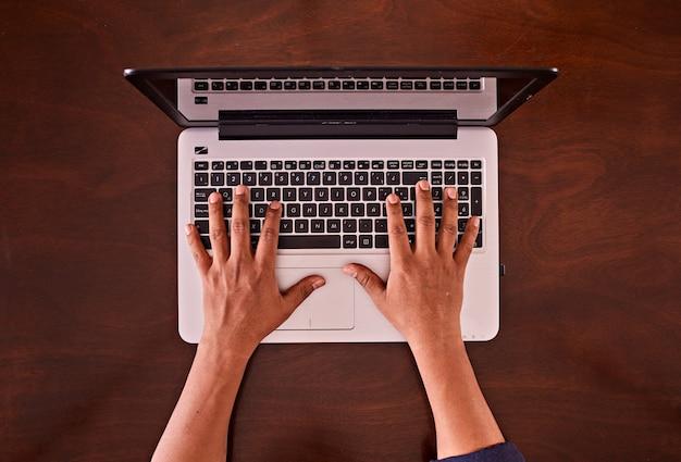 Mannhände, die auf laptop-tastatur tippen. auf einem schreibtisch