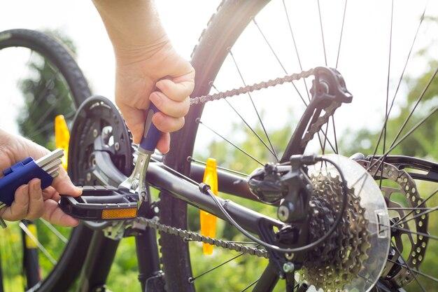 Mannhände, die das fahrrad durch reparaturschlüssel reparieren
