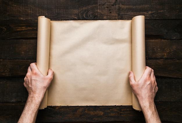 Mannhände, die gestresste papierrolle auf altem barwoodhintergrund halten. kreatives konzept der fernweh-expedition. leerer raum, platz für text, schriftzug. horizontales banner-modell.