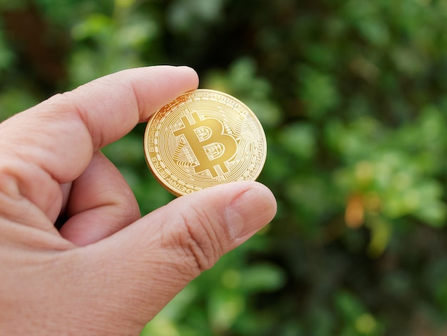 Mannhände, die goldenes bitcoin zeigen. digitales symbol einer neuen virtuellen währung.