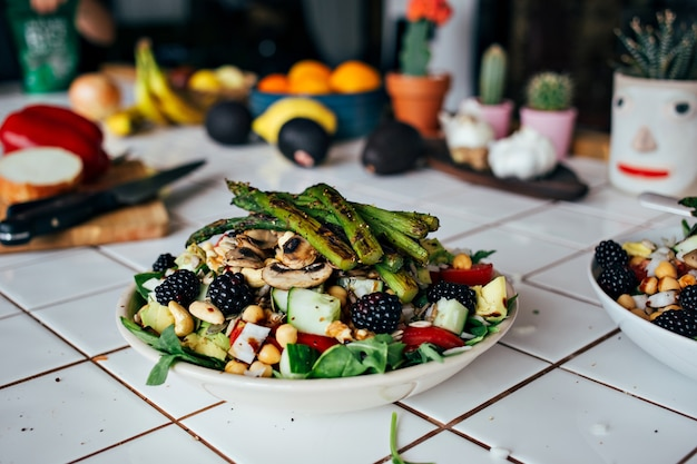 Mannhände, die großen tiefen teller voll des gesunden paläo-vegetarischen salats halten, der aus frischen biologischen biologischen bestandteilen, gemüse und früchten, beeren und anderen ernährungsphysiologischen dingen hergestellt wird