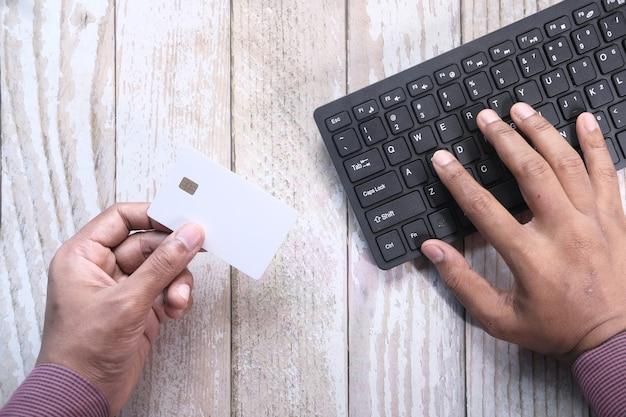 Mannhände, die kreditkarte halten und tastatureinkauf online verwenden, von oben nach unten