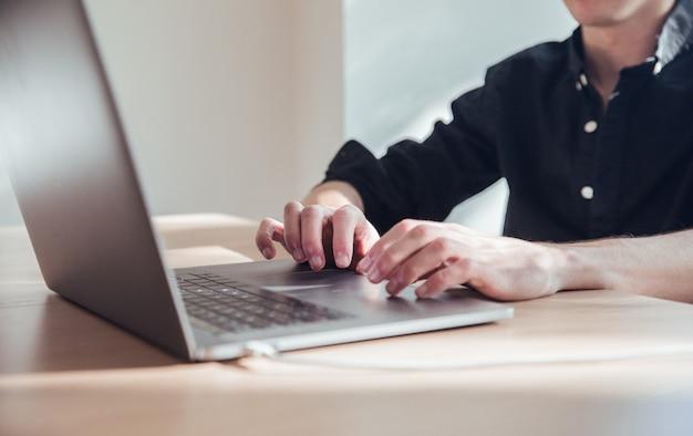 Mannhände, die mit schwarzem laptop im büro arbeiten