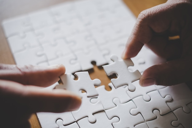 Mannhände, die paarpuzzlespielstück im büro anschließen. ziele und strategie