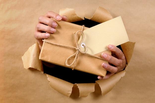 Mannhände, die paket durch heftigen hintergrund des braunen papiers liefern oder geben