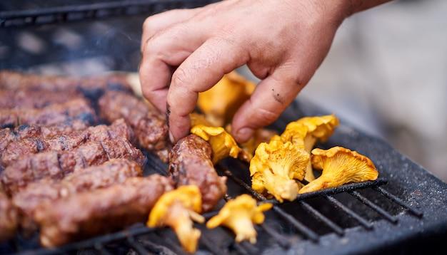 Mannhände, die rumänisches mititei kochen