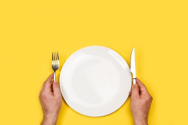 Mannhände halten gabel und messer auf einem weißen teller auf gelbem hintergrund