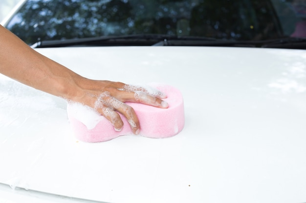 Mannhände halten schwamm für das waschen des weißen autos