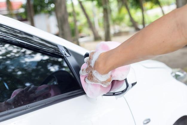 Mannhände halten schwamm zum waschen des autos