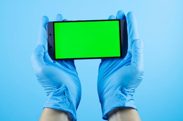 Mannhände halten telefon im schützenden medizinischen handschuh, coronavirus covid-19-virus