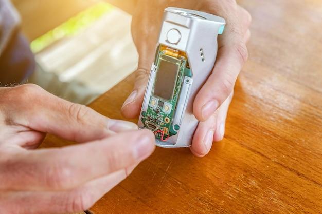 Mannhände reparieren modernes vaporizer-e-cig-gadget, um e-liquid zu verdampfen. wartung des mech-mod-dampfgeräts für elektronische geräte. reparaturservice für dampfgeräte.