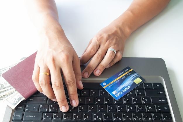 Mannhände unter verwendung der laptop-computers und der kreditkarte. reisepass und geld