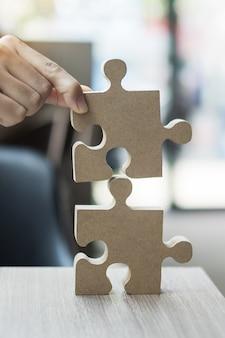 Mannhände verbinden paar puzzle über tisch, geschäftsmann hält holzpuzzle im büro.