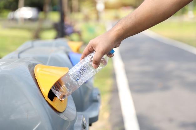Mannhände werfen leere plastikflasche in den müll