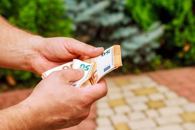 Mannhände zählen euro-banknoten. geld zählen.