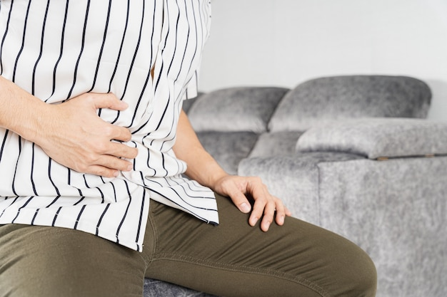 Mannhand berührt bauch, taille oder leberposition beim sitzen auf dem sofa.