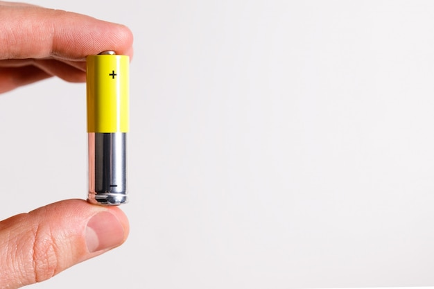 Mannhand, die alkalische batterie aa größe, nah oben, lokalisiert auf weißem hintergrund mit kopienraum hält.