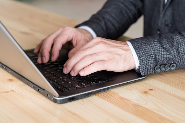 Mannhand, die auf laptop tippt. remote-job und online-geschäft. freiberufliche arbeit.