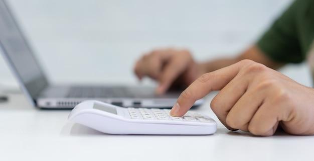 Mannhand, die auf taschenrechner zur berechnung über monatsausgaben drückt
