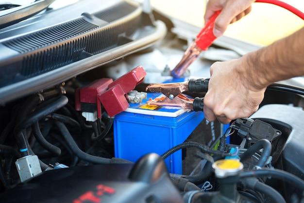 Mannhand, die batterieladekabel hält, die energie an eine leere batterie übertragen