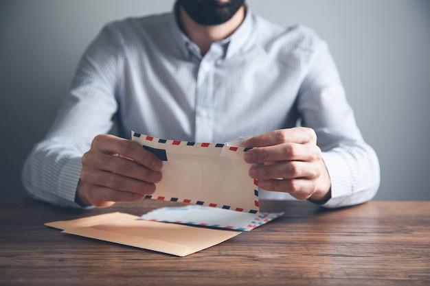 Mannhand, die briefe auf schreibtisch hält