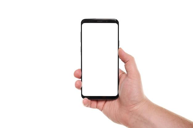 Mannhand, die den leeren bildschirm des schwarzen smartphones mit modernem rahmenlosem design lokalisiert auf weißem hintergrund hält