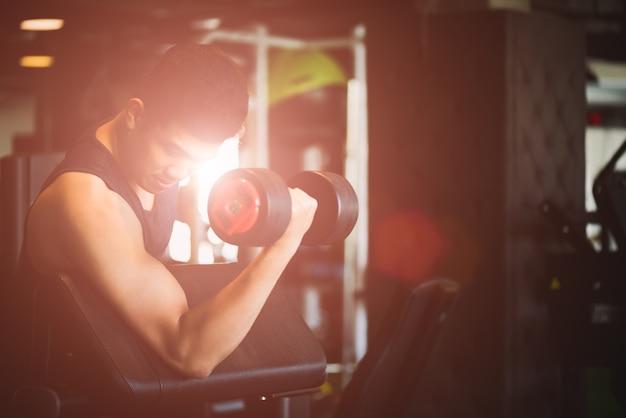 Mannhand, die dummkopfübung in der turnhalle hält. fitness muskulöser körper mit schwarzen gewichten
