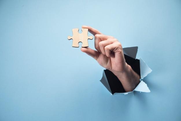 Mannhand, die ein puzzleteil auf einer blauen szene hält
