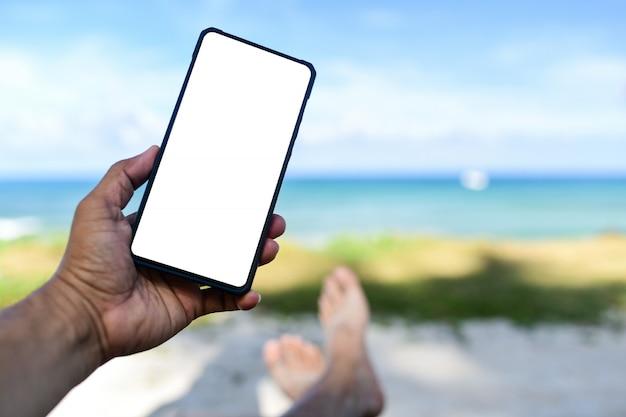 Mannhand, die ein telefon des leeren raumes des weißen bildschirms hält er schlief auf dem strand.