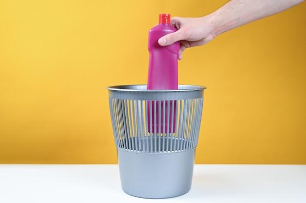 Mannhand, die eine leere plastikwasserflasche in den mülleimer wirft