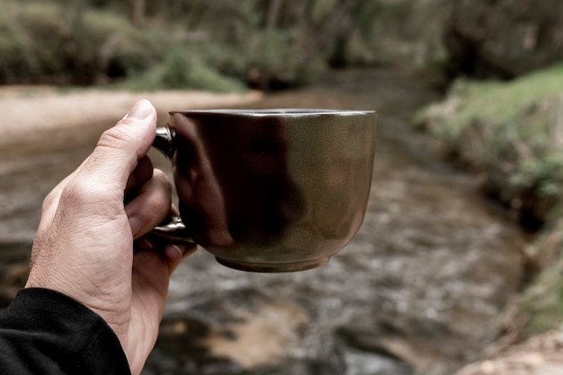 Mannhand, die eine tasse im wald, herbstkonzept hält