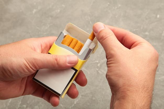 Mannhand, die eine zigarettenschachtel hält