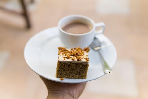 Mannhand, die einen tasse kaffee und einen kuchen hält.