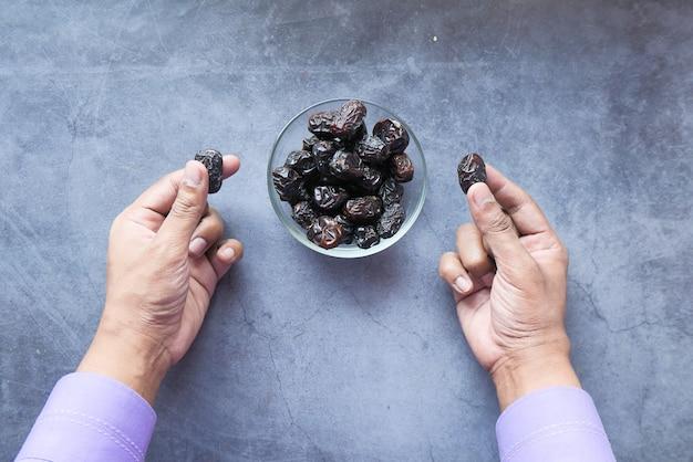 Mannhand, die frische dattelfrucht in einer schüssel auf tisch isst