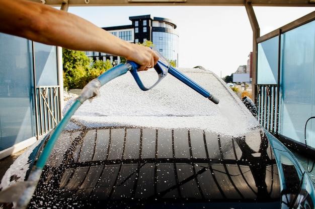 Mannhand, die front des autos wäscht