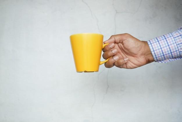 Mannhand, die gelben farbbecher gegen weiße wand hält
