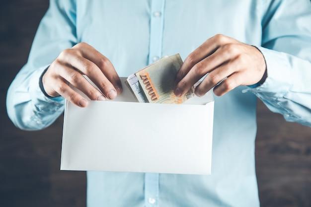 Mannhand, die geld mit brief hält