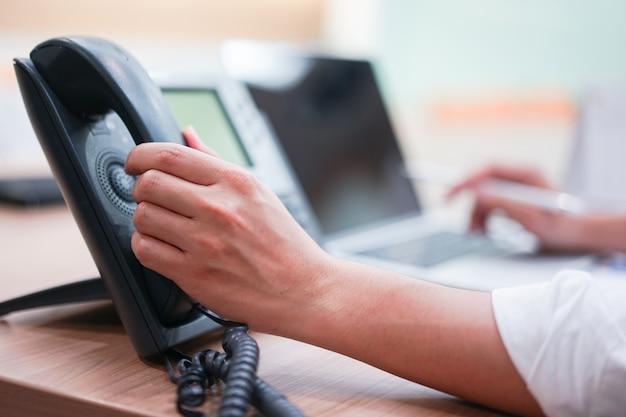Mannhand, die hörer hält, um anruf zum kunden zu machen