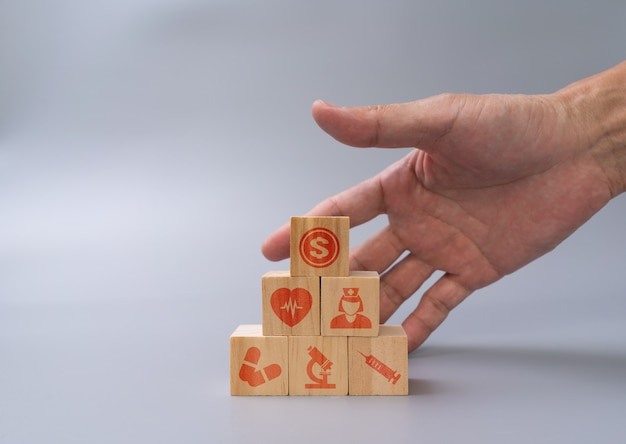 Mannhand, die holzblöcke mit gesundheits- und medizinischem symbolstapeln, medizinisches krankenversicherungskonzept anordnet