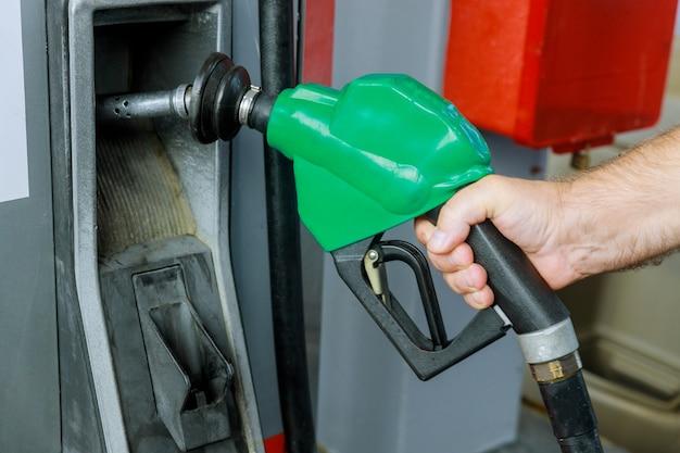 Mannhand, die kraftstoffdüse hält, um gas an der tankstelle hinzuzufügen