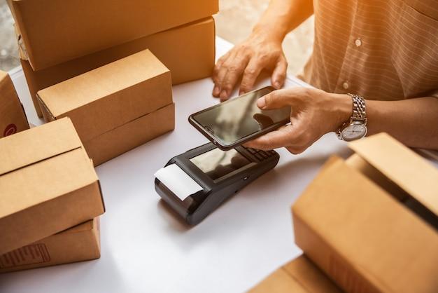 Mannhand, die kreditkartenleser nfc-technologie-geldmaschine hält.