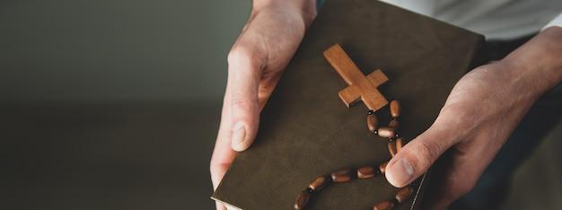 Mannhand, die kreuz auf bibelbuch hält