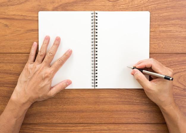 Mannhand, die notizbuch auf holzhintergrund schreibt