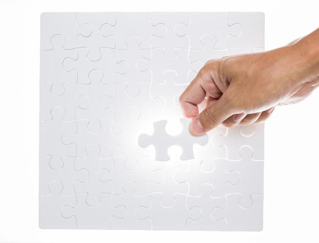 Mannhand, die puzzlestück hält