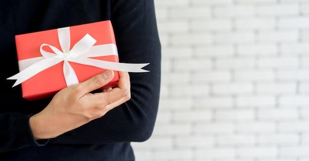 Mannhand, die rote geschenkbox für verkaufssaison der frohen weihnachten hält
