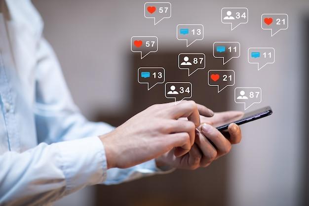 Mannhand, die smartphone mit bunten anwendungssymbolen herum verwendet