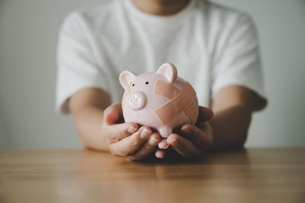 Mannhand, die sparschwein auf holztisch hält. konzept, geld zu sparen und unternehmensinvestitionen zu finanzieren