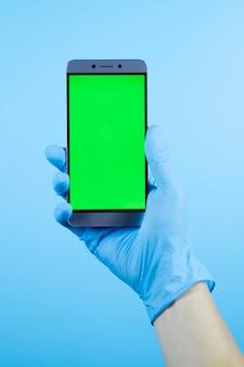 Mannhand, die telefon im medizinischen schutzhandschuh, coronavirus covid-19-virus hält